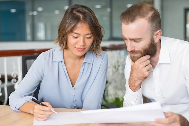 Nachdenkliche geschäftsexperten, die marketingbericht analysieren