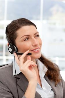 Nachdenkliche geschäftsfrau, die an den telefonen unter verwendung der kopfhörer spricht