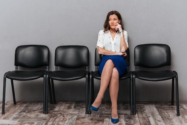 Nachdenkliche geschäftsfrau, die auf stühlen wartet
