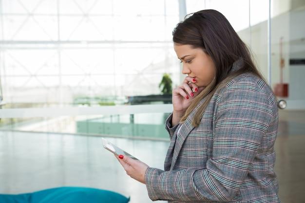 Nachdenkliche geschäftsfrau, die draußen tablette verwendet