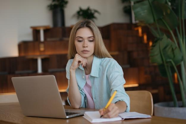 Nachdenkliche geschäftsfrau, die laptop-computer benutzt, notizen macht, arbeitsprojekt
