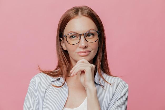 Nachdenkliche geschäftsfrau hält kinn, schaut nachdenklich zur seite und trägt eine brille
