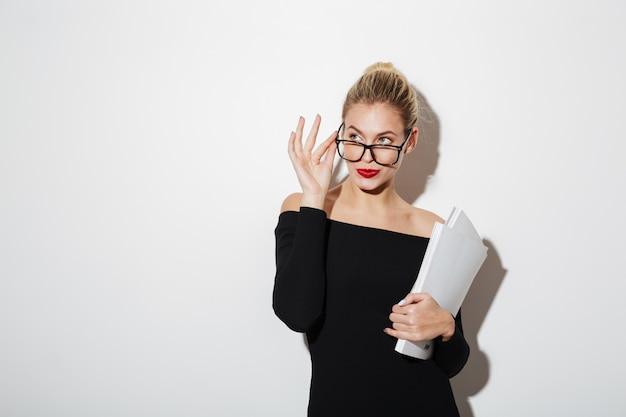 Nachdenkliche geschäftsfrau im kleid und in brillen, die dokumente verwahren
