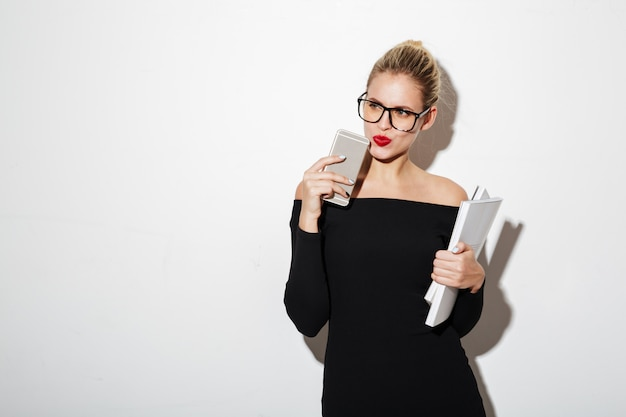 Nachdenkliche geschäftsfrau im kleid und in brillen, die weg schauen
