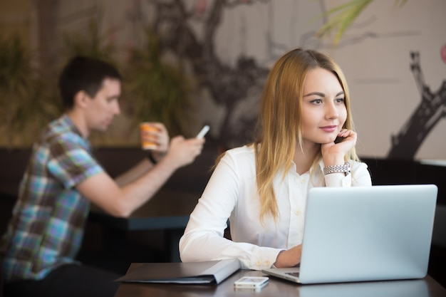 Nachdenkliche geschäftsfrau in dem coffee-shop arbeiten