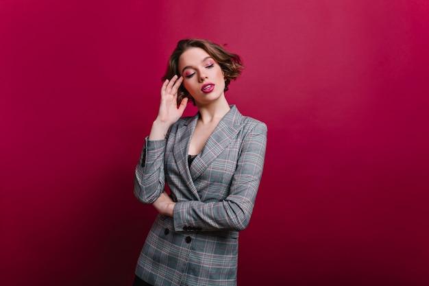 Nachdenkliche geschäftsfrau mit rosa make-up, das auf rotweinwand aufwirft. ernsthafte junge dame in grauer jacke mit glänzenden kurzen haaren, die an etwas denken.