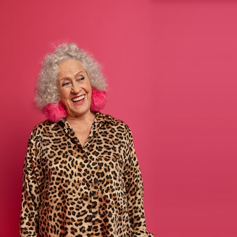 Nachdenkliche glückliche ältere frau, die froh ist, in rente zu sein, schaut positiv zur seite, hat lockiges haar, make-up und faltiges gesicht, trägt stilvolle kleidung, trifft gäste während ihrer geburtstags- oder ruhestandsfeier