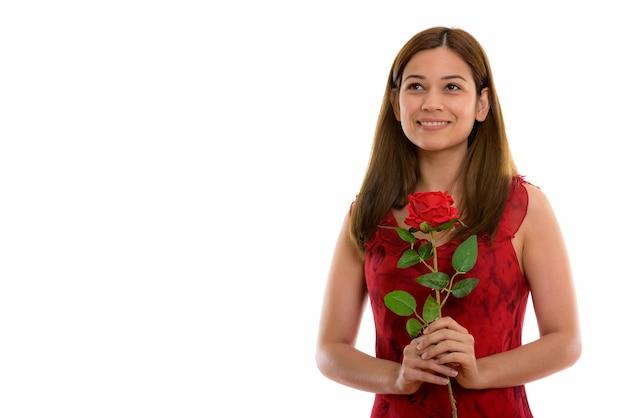 Nachdenkliche glückliche junge frau, die lächelt und rote rose bereit hält