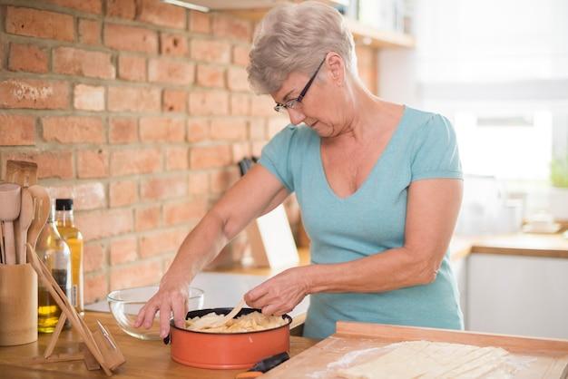 Nachdenkliche großmutter backt köstlichen apfelkuchen