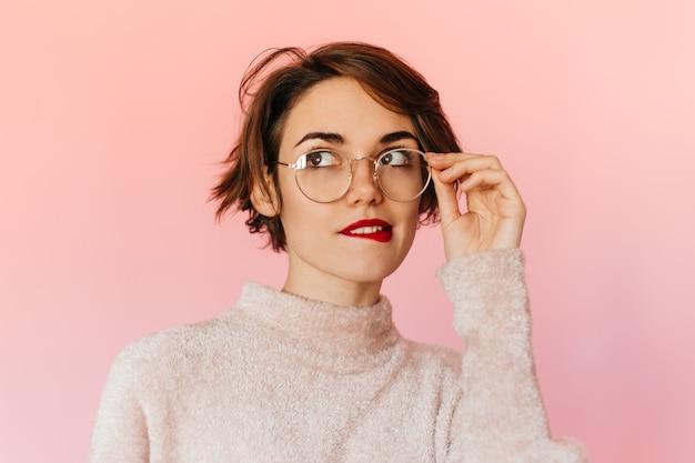 Nachdenkliche gutaussehende frau, die brille berührt
