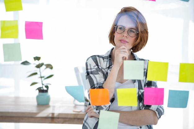Nachdenkliche hipster frau, die in ihrem büro steht und notizen über alles liest