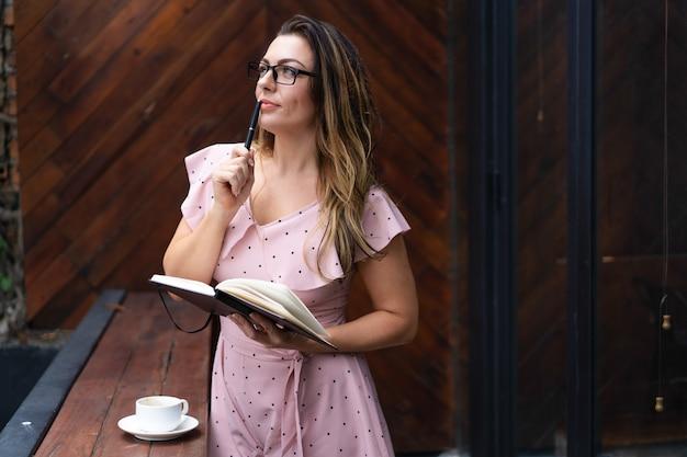 Nachdenkliche hübsche frau, die notizbuch im café hält