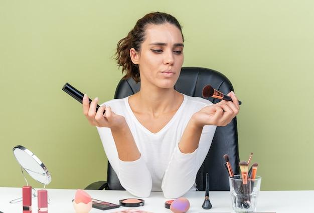 Nachdenkliche hübsche kaukasische frau, die am tisch mit make-up-tools sitzt und make-up-pinsel hält und betrachtet, isoliert auf olivgrüner wand mit kopierraum