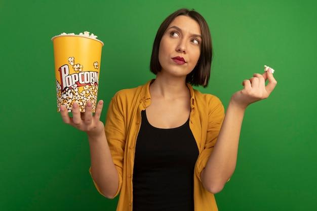 Nachdenkliche hübsche kaukasische frau hält eimer popcorn und schaut auf grün auf