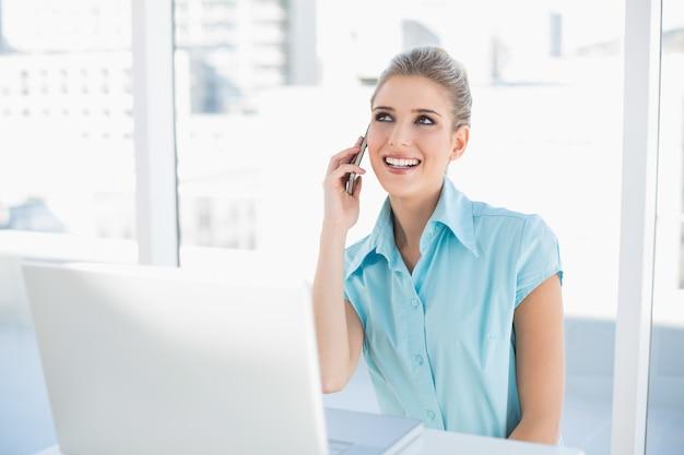 Nachdenkliche intelligente geschäftsfrau am telefon bei der anwendung des laptops