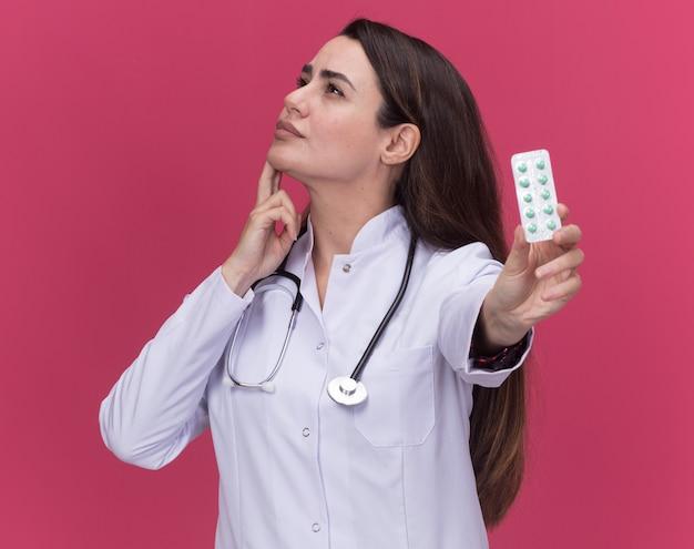 Nachdenkliche junge ärztin, die ein medizinisches gewand mit stethoskop trägt, legt die hand auf das kinn und hält eine packung medizin auf der seite