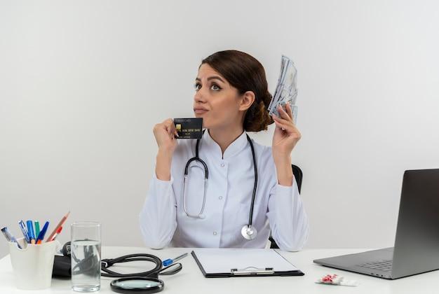 Nachdenkliche junge ärztin, die medizinische robe und stethoskop trägt, sitzt am schreibtisch mit medizinischen werkzeugen und laptop, die kreditkarte und geld halten, die lokal suchen
