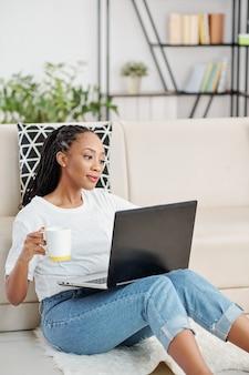 Nachdenkliche junge afroamerikanische frau, die auf dem boden sitzt, kaffee trinkt und webinar online auf ihrem laptop sieht