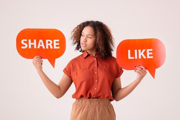 Nachdenkliche junge afroamerikanische frau, die share and like-tags hält und social-media-aktivitäten auswählt