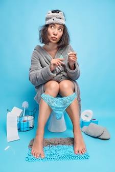 Nachdenkliche junge asiatin malt nägel, während sie auf der toilette sitzt, fühlt sich entspannt, trägt schlafmaske und bademantel-spitzenhöschen, die an den beinen heruntergezogen sind, denkt an etwas, das isoliert auf blauer wand wegschaut