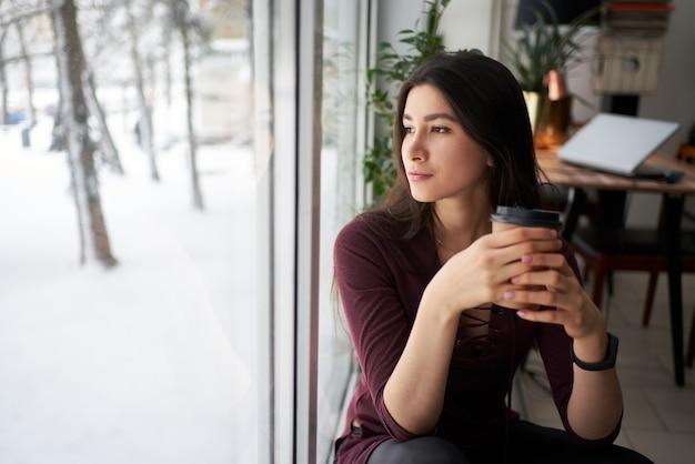 Nachdenkliche junge asiatische brünettefrau mit tasse kaffee, die durch das fenster im winter schaut