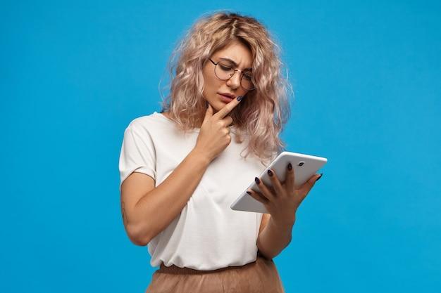 Nachdenkliche junge attraktive frau, die im internet surft, weltnachrichten liest oder e-mails auf digitalem tablet überprüft. nachdenkliches süßes mädchen in der brille, das tragbaren computer des generischen touchpads für fernarbeit verwendet