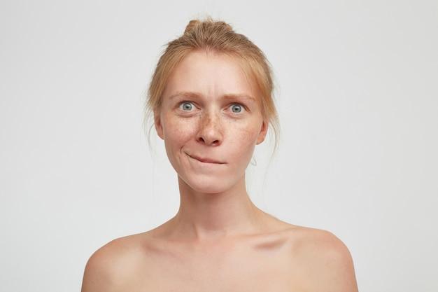 Nachdenkliche junge attraktive rothaarige frau mit brötchenfrisur, die unterlippe beißt und verwirrt in die kamera schaut und über weißem hintergrund mit nackten schultern aufwirft
