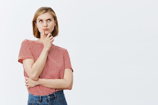 Nachdenkliche junge blonde frau, die rätsel löst, ratlos aufschaut und nachdenkt