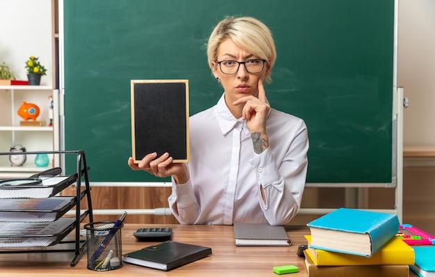 Nachdenkliche junge blonde lehrerin mit brille, die am schreibtisch mit schulmaterial im klassenzimmer sitzt und eine mini-tafel zeigt, die die hand am kinn hält und nach vorne schaut