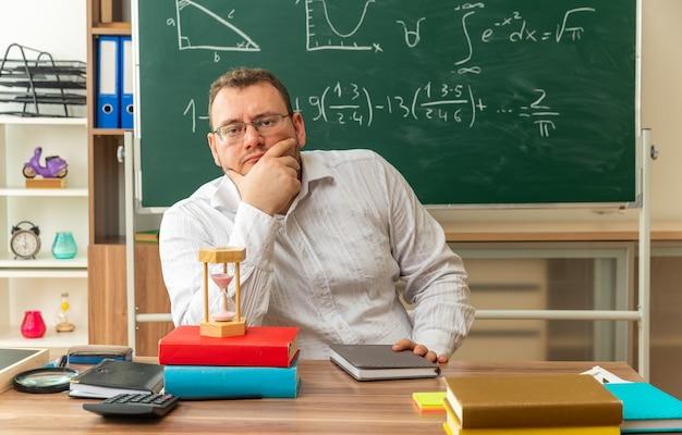 Nachdenkliche junge blonde lehrerin mit brille, die am schreibtisch mit schulwerkzeugen im klassenzimmer sitzt und die hand am kinn hält und in die kamera schaut