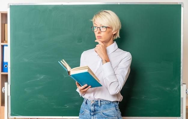 Nachdenkliche junge blonde lehrerin mit brille im klassenzimmer, die vor der tafel steht und ein buch hält, das die hand am kinn hält und auf die seite mit kopienraum schaut