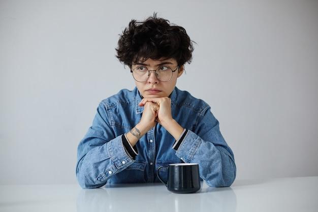Nachdenkliche junge braunäugige kurzhaarige lockige brünette frau in brille hält ihren kopf auf erhobenen händen und schaut vor sich mit ernstem gesicht, isoliert