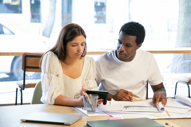 Nachdenkliche junge designer, die blaupausen und tablettbildschirm betrachten, am tisch sitzen, zusammenarbeiten und sprechen