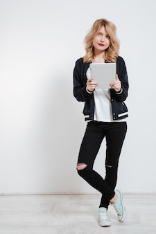Nachdenkliche junge frau des teenagers, die tablet-computer denkt und hält