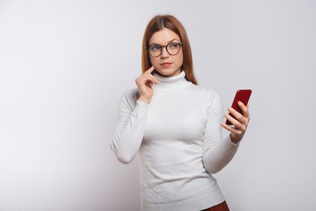 Nachdenkliche junge frau, die smartphone hält