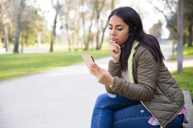 Nachdenkliche junge frau im surfenden netz der jacke auf smartphone