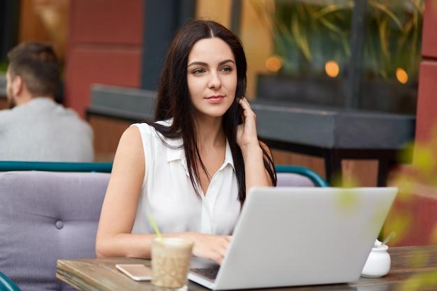 Nachdenkliche junge frau in eleganter bluse, schaut nachdenklich in die ferne, arbeitet am laptop, trinkt aromatischen kaffee