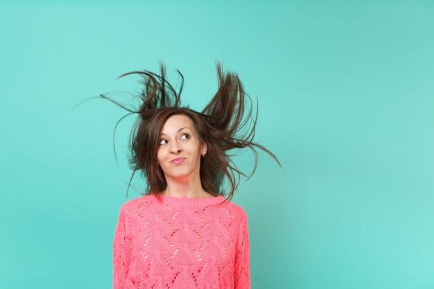 Nachdenkliche junge frau in gestricktem rosa pullover mit flatternden haaren, die einzeln auf blautürkisem wandhintergrund nachschlagen, studioporträt. menschen aufrichtige emotionen, lifestyle-konzept. kopieren sie platz.