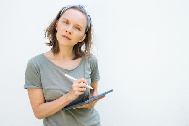 Nachdenkliche junge frau mit stift und tablette, die am projekt arbeitet