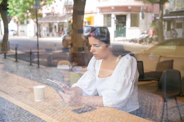 Nachdenkliche junge geschäftsfrau, die am schreibtisch im gemeinsamen arbeitsraum oder im kaffeehaus unter verwendung der tablette sitzt