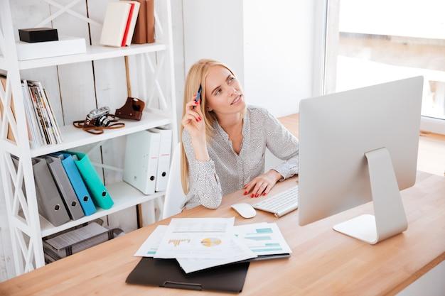 Nachdenkliche junge geschäftsfrau, die an ihrem arbeitsplatz sitzt und aufschaut