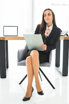 Nachdenkliche junge geschäftsfrau, die auf dem stuhl hält klemmbrett und stift in ihrer hand sitzt