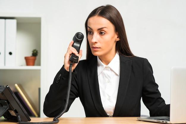 Nachdenkliche junge geschäftsfrau, die im büro hält telefonhörer sitzt