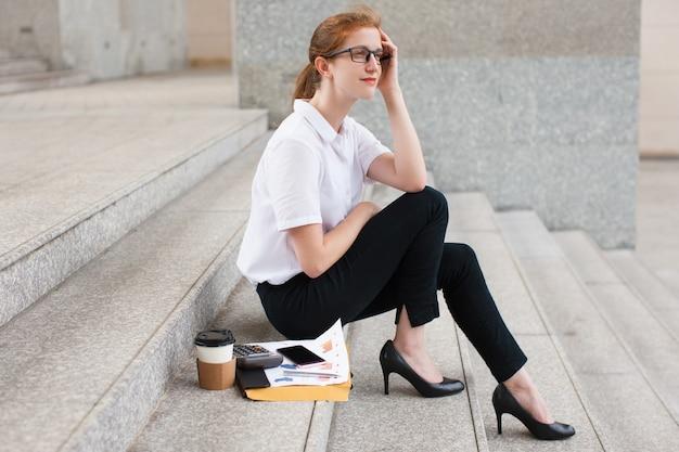 Nachdenkliche junge geschäftsfrau sitzt auf treppe