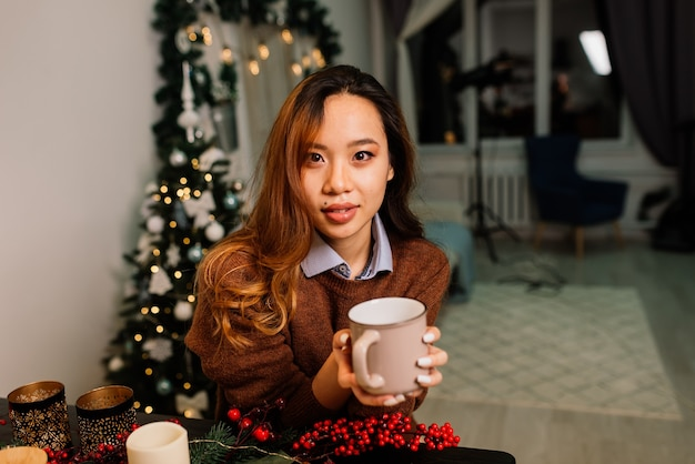 Nachdenkliche junge hübsche asiatische frau mit brennenden kerzen an heiligabend, die wünsche macht