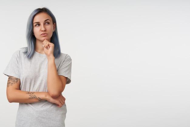 Nachdenkliche junge hübsche dame mit kurzem haarschnitt, die ihr kinn zur hand lehnt und augenbraue hochzieht, während sie nachdenklich beiseite schaut und auf weiß steht
