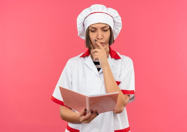 Nachdenkliche junge köchin in der kochuniform, die notizblock hält und betrachtet und hand auf kinn lokalisiert auf rosa wand setzt
