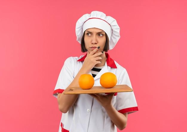 Nachdenkliche junge köchin in der kochuniform, die schneidebrett mit orangen auf ihm hält, die ihr kinn berühren und seite betrachten, die auf rosa wand lokalisiert wird
