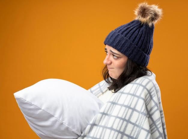 Nachdenkliche junge kranke frau, die robe wintermütze in plaid gewickelt steht in profilansicht umarmendes kissen, das gerade lokalisiert auf orange wand steht