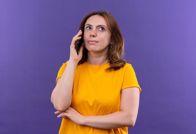Nachdenkliche junge lässige frau, die am telefon auf isolierter lila wand mit kopienraum spricht